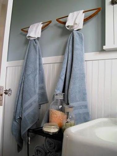 Los colgadores de madera colgados en la pared al revés se convierten en un estupendo toallero en el baño.