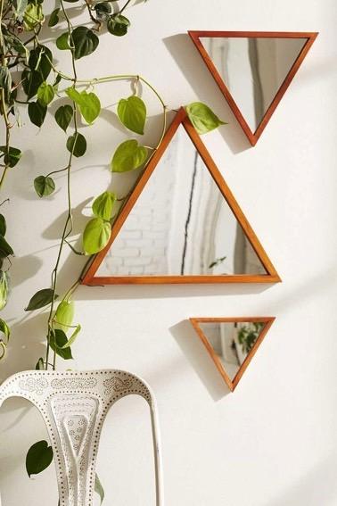 Pequeños espejos de forma triangular están muy bien dispuestos en una pared blanca de forma decorativa para dar dinamismo y cierto prestigio a la habitación.