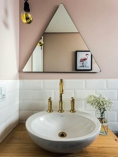 El baño tiene un espejo en forma de triángulo colocado en la pared rosa pastel, justo encima de los azulejos blancos del metro, todo subrayado con toques dorados.