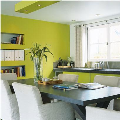 Muebles de cocina verde lima y pintura con encimera de granito gris a juego con el tablero de la mesa.  Alrededor de la mesa hay sillones viejos vestidos con una funda de algodón blanco que se hace eco de la pintura en el techo y el marco del ventanal.  Pintura V33