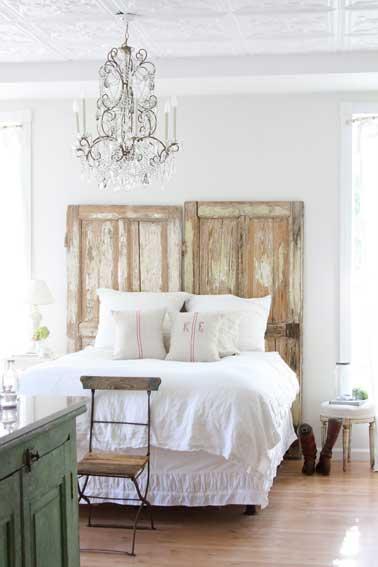 La simplicidad es elegante en un dormitorio blanco con un cabecero provisto de 2 puertas con apariencia de madera flotante colocadas en la cabecera de la cama sin otras transformaciones.  Lo más destacado de un estilo bohemio chic es la lámpara de araña de cristal blanco facetado.