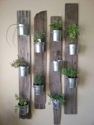 Muro verde realizado con macetas de hierro fijadas sobre tablas de recup.  Limpias y lijadas, las tablas se dejan en estado crudo para sacar las plantas aromáticas.
