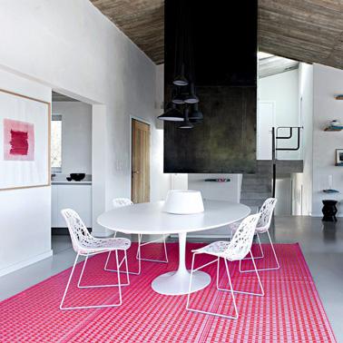 Un suelo rosa en el salón para alegrar una decoración en blanco y negro, con esta alfombra Fly con motivos gráficos