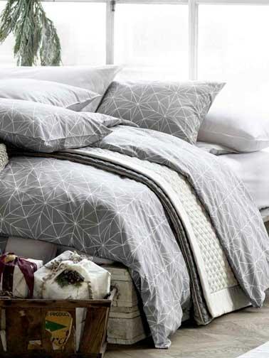 Piense en la ropa de cama para hacer la decoración envolvente de la habitación.  Aquí, una colcha de H&M Home con motivos geométricos en tonos suaves combina con los colores del dormitorio