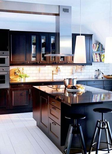 Una combinación de estilos muy acertada en esta cocina negra de diseño con una isla central que contrasta con un salpicadero en azulejos blancos de metro ultra elegantes