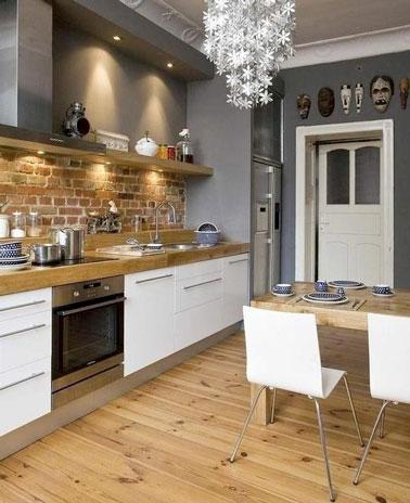 Un toque rústico está invitado a la decoración de esta acogedora cocina con un salpicadero de ladrillo acentuado por una encimera de madera y un hermoso piso de parquet.