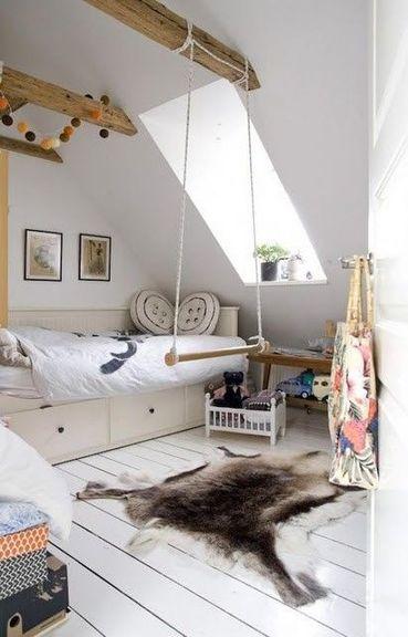Este dormitorio con pendiente parcial se ha pintado de blanco para que entre luz y parezca más espacioso.  Las vigas expuestas están barnizadas para un efecto natural.