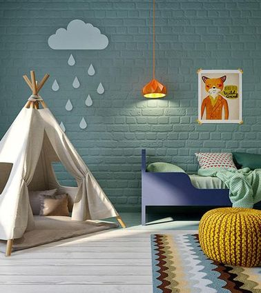 La pared de ladrillos en el dormitorio de esta niña se ha pintado de azul para darle un ambiente relajante.  Nos encanta la lámpara de araña de diseño, el puf tejido y la decoración de pared DIY.
