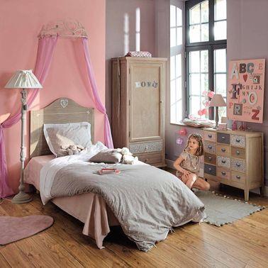 Este dosel de cama de la casa del mundo le da un toque de país de las hadas a este dormitorio de princesa rosa.  El resto de la decoración es más sobria para evitar un ambiente ajetreado.