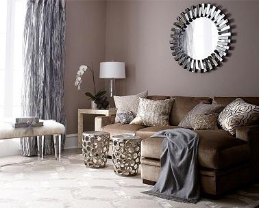 Un salón luminoso gracias al color topo de las paredes que contrasta con el suelo blanco.  El sofá marrón y la cortina gris y los accesorios a cuadros combinan con la atmósfera envolvente de esta sala de estar.  El espejo y las pequeñas mesitas de metal dan un toque más moderno a toda la estancia.