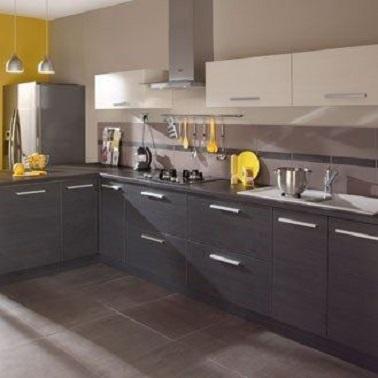 El color topo de la pared principal de esta cocina contrasta perfectamente con el mobiliario gris oscuro.  Los muebles altos de color blanco, por su parte, armonizan a la perfección en la suavidad del ambiente mientras que la pequeña sección de la pared y los pocos accesorios amarillos añaden un toque de fantasía a toda la estancia.
