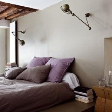 El color topo de la pared de este dormitorio se ve reforzado por el tono morado de las sábanas.  El conjunto da un dormitorio con una decoración muy actual y un ambiente sereno.