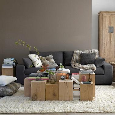 Una pared de color topo junto a una pared gris claro: la apuesta tiene éxito en este salón.  Los muebles de madera clara y la alfombra blanca iluminan la habitación y la hacen más agradable.  Finalmente, el sofá gris oscuro en el centro afirma el carácter de la habitación.