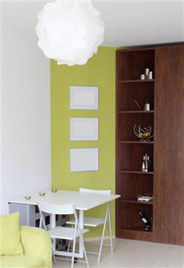 comedor color verde manzana, blanco en contraste con armario de estantería de roble oscuro