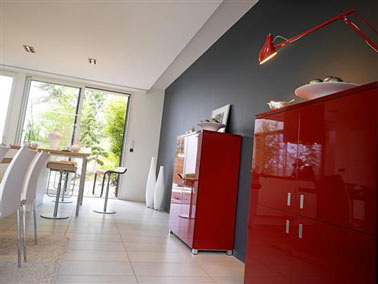 decoración moderna del comedor con muebles blancos en contraste con el acabado mate de la pared gris antracita y dos aparadores lacados en rojo brillante