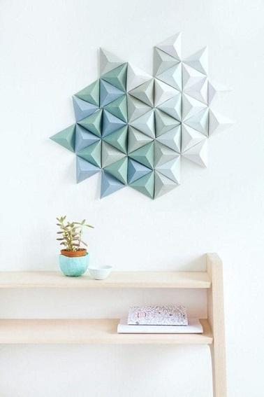 Una nube de origami se pega en esta pared ofreciendo una decoración en relieve única en la tendencia de las formas geométricas.  ¡Una idea fácil de rehacer en casa!