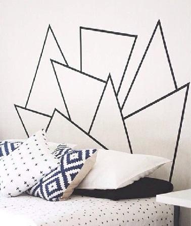Las formas geométricas con cinta adhesiva también son una solución para ahorrar espacio.  En el dormitorio, esta técnica crea un cabecero.