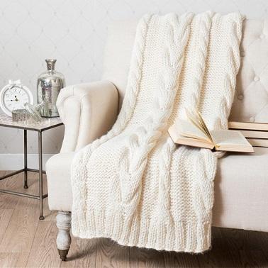 Un plaid tejido con pespuntes gruesos en un color blanquecino.