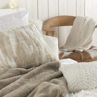 Cojín de cama grande de color beige suave para vestir la cama de una habitación acogedora.