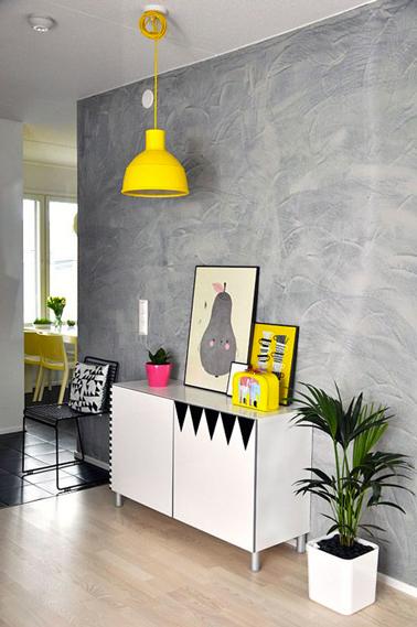 En una sala de estar moderna, una lámpara colgante amarilla para resaltar el gris del yeso decorativo y calentar los colores neutros dominantes.