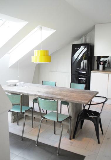 Un ajat-jour amarillo brillante para arreglar la decoración de una cocina blanca en el ático con sillas verde mar