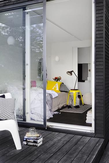 Armonía de tonos grises y blancos en el dormitorio de esta niña realzado por un taburete Tolix amarillo limón que hace las veces de mesita de noche.