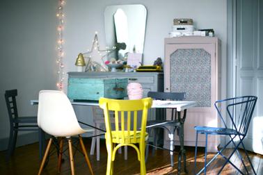 Las sillas que no combinan están de moda para la decoración del comedor.  En este, la única silla amarilla se usa para romper la monocromía del verde azulado.