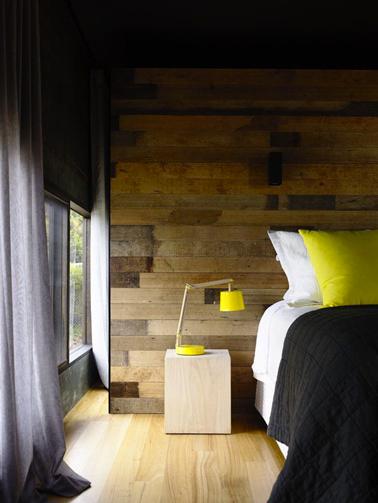 decoración de dormitorio para adultos con una magnífica pared de paneles de madera para la cabecera mejorada con ropa de cama amarilla y negra
