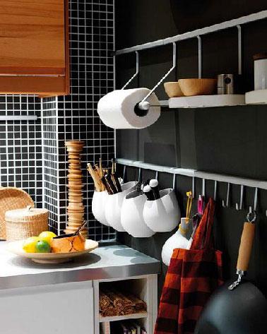 Una idea inteligente de usar la pared del fregadero para crear espacio para los utensilios en cuencos suspendidos de una barra de acero inoxidable.