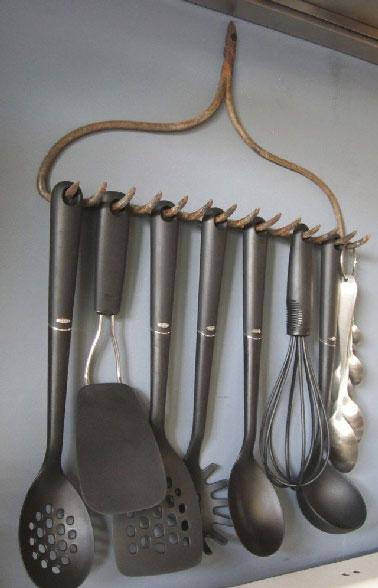 Combine la decoración recuperada y la organización del almacenamiento de la cocina con un rastrillo para colgar las espátulas sobre la estufa, una punta de decoración barata.