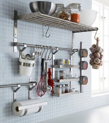 Un buen consejo para agrupar accesorios de cocina en una sola pared, barras de acero inoxidable equipadas con ganchos colocadas debajo de una parrilla Ikea.  Los tarros de especias y los utensilios son de fácil acceso.