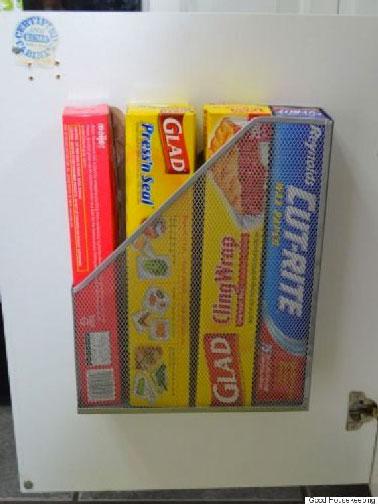 Una idea práctica para solucionar la desorganización del almacenamiento de rollos de aluminio y film transparente: una carpeta a modo de canasta sujeta al interior de un mueble de cocina.