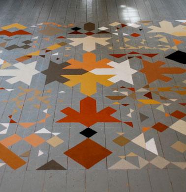 Para repintar el parquet de este salón, un precioso conjunto de estampados realizados con cuatro colores de pintura para imitar una alfombra en el suelo