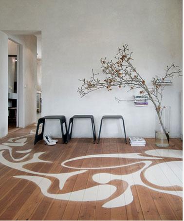 Salón de diseño con suelo de parquet decorado con grandes arabescos pintados en blanco sobre parquet de color roble medio