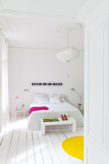 Pinte el parquet de un dormitorio para adultos de blanco con un gran círculo de pintura amarilla para darle un toque contemporáneo.