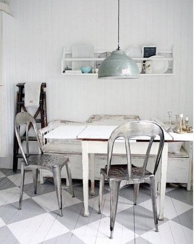 Para un efecto loft, el piso de la cocina está pintado con grandes patrones de azulejos escalonados en gris y blanco.