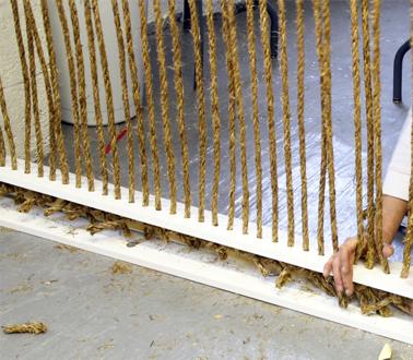 Para hacer un tabique interior y separar los espacios, corte trozos de cuerdas de fibra natural y átelos sobre listones perforados.