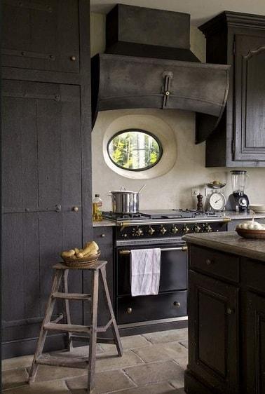 En esta cocina, la pintura de los muebles y la isla central gris marengo acentúan el carácter auténtico del suelo de baldosas de tierra y la campana de cobre de época.