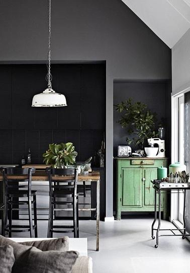 Una cocina abierta repintada en gris marengo y negro para enfatizar su estilo industrial.  La pintura se utiliza aquí como revelador para resaltar los muebles de madera y hierro con la complicidad del pequeño mueble de almacenaje repintado en verde agua.