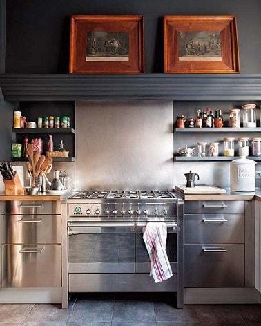 Una elegante cocina gris con pintura gris carbón en la viga y la parte superior de la pared sobre un salpicadero gris perla y nichos de almacenamiento repintados en gris ratón, utilizados para el color del piso de baldosas.