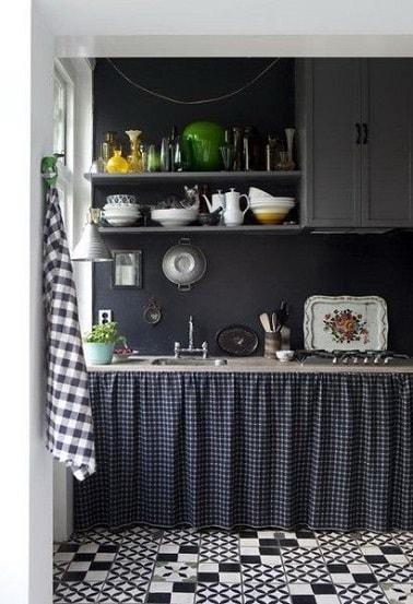 En esta pequeña cocina, la pintura en 2 tonos de gris antracita resalta el suelo de baldosas de cemento en blanco y negro y los toques de amarillo y verde que aportan la vajilla y los accesorios de cocina.