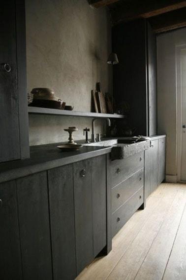 Esta decoración de cocina con fregadero de piedra negra y paredes de hormigón encerado greige toma el lado del uso de pintura gris carbón para los muebles de cocina de madera.