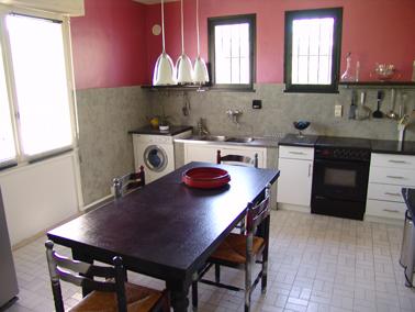 Pintura de azulejos de cocina con pintura gris efecto cemento.  Encimera de pared alta pintada con pintura efecto metalizado rosa.