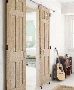 Tendencia vintage para estas dos puertas recuperadas montadas sobre una barandilla de hierro y ruedas a modo de tabique corredizo para separar el baño de un dormitorio de adultos.