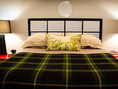secuestrar una vieja puerta de vidrio para hacer un cabecero le da un aire japonés al dormitorio cuando se fija horizontalmente sobre la cama.