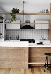 El salpicadero de azulejos adhesivos formado por pequeños cuadrados blancos combina a la perfección con la decoración de esta cocina de madera y blanco ultra acogedor