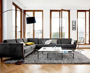 El diseño se muestra en la sala de estar con este sofá esquinero.  Moderno con su revestimiento de tela gris oscuro, combina comodidad con una estética contemporánea.