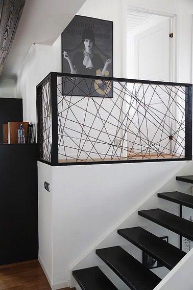 Justo al lado de las escaleras, una barandilla de hierro negro de hiper diseño encaja a la perfección en esta moderna decoración interior dominada por el blanco y el negro.