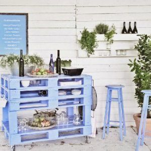 Para realizar esta mesa, haz 4 tarimas de madera montadas sobre ruedas y pintadas de azul.  Otro palet se utiliza para almacenar las botellas.