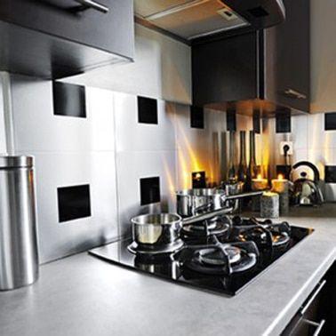 Un backsplash adhesivo en baldosas adhesivas de aluminio con un juego de baldosas adhesivas negras que nos recuerda los colores dominantes de la cocina negra y acero inoxidable
